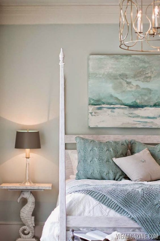 beach decor style bedroom with seahorse lamp sea painting and wooden bed head