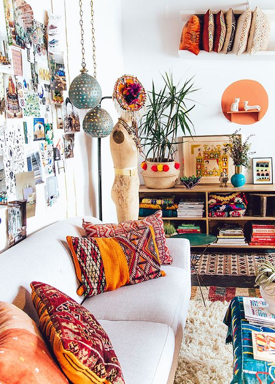 eclectic bohemian style bedroom wth ethnic priint cushions indoor prints and hanging lanterns