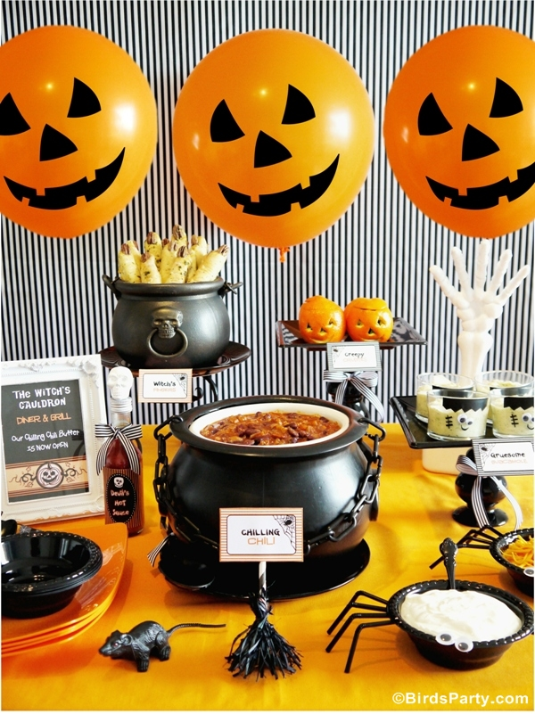 halloween table layout with cauldrons pumpkin balloons