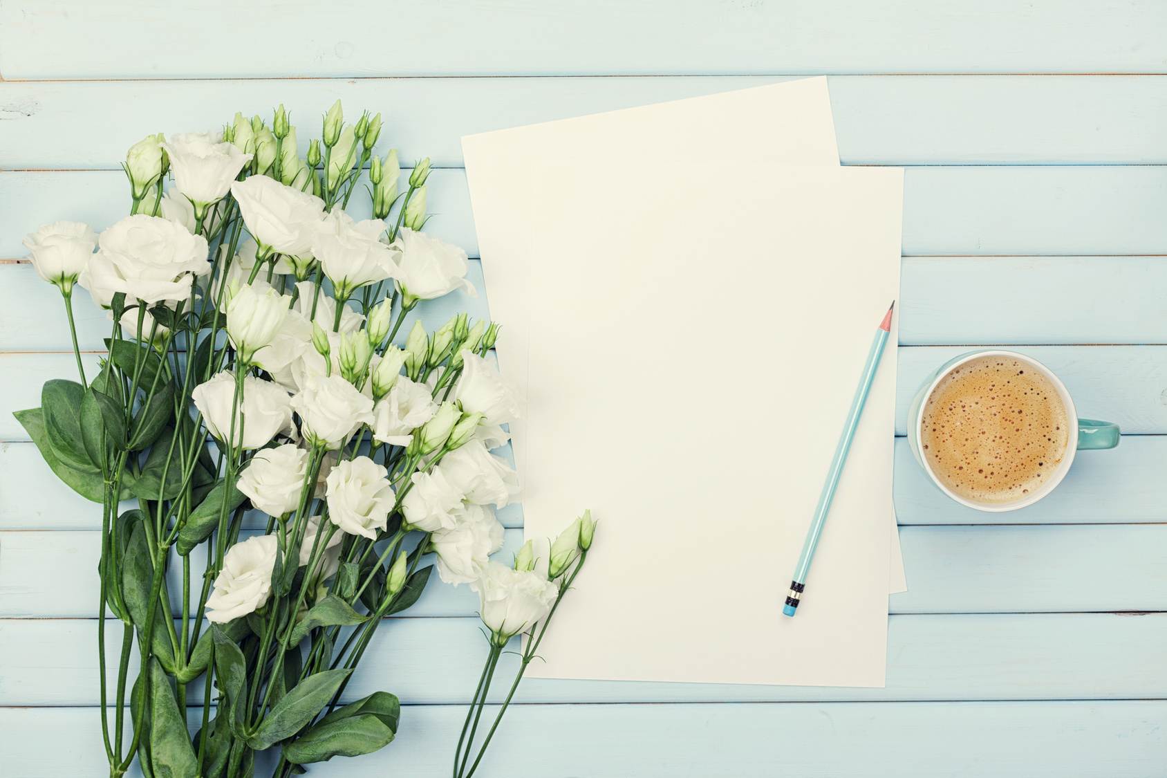 Morning coffee cup, empty paper list, pencil, and bouquet of white flowers eustoma on blue rustic table from above. Woman working desk. Cozy breakfast. Flat lay styling.