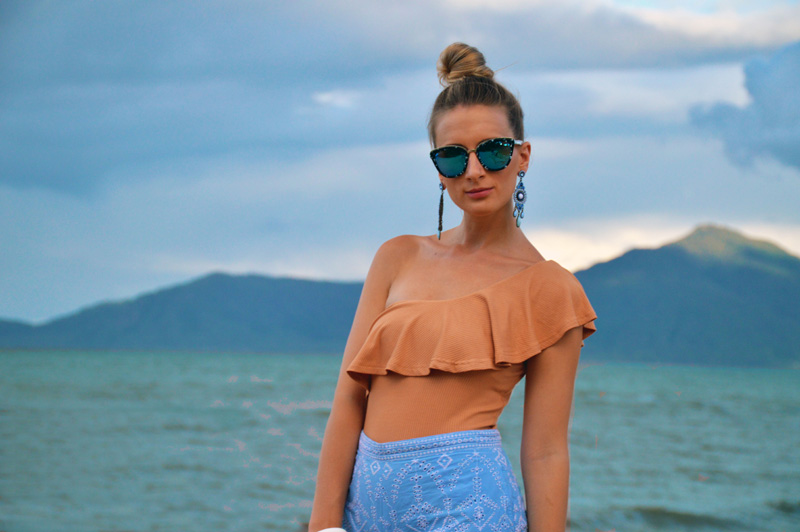 girl-wearing-one-shoulder-top-embroidered-shorts-marble-sunglasses
